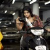 Ayesha Takia sitting on a scooty