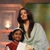 Aishwarya Rai felicitates a child at the Tribute to the Legend of Pure Love concert