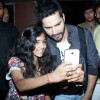 Varun poses for a selfie with a young fan