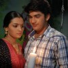 Mohan and Bhakti standing with a candle