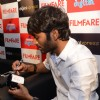 Dhanush signs a mug at the Filmfare Readers Meet at the Reliance Digital Store