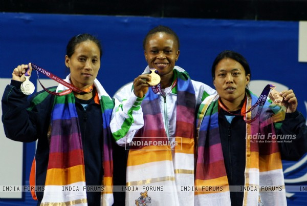 The winner of first Gold medal of the 19th Commonwealth Games, Nigeria's Augustina Nkem (center) with India's  Siver medal winner Sonia Chanu (left)  and Bronze medal winner Sandhya Rani devi(Right) at the 48-kg category womens weightlifting