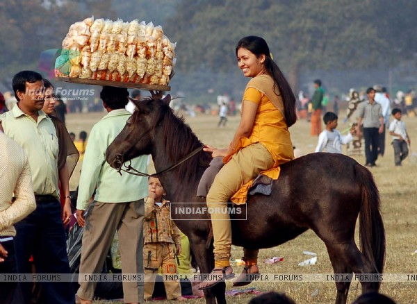 A lady tourist enjoys horse ride during the first day of New Year 2011 in Kolkata Maidan on Saturday. .