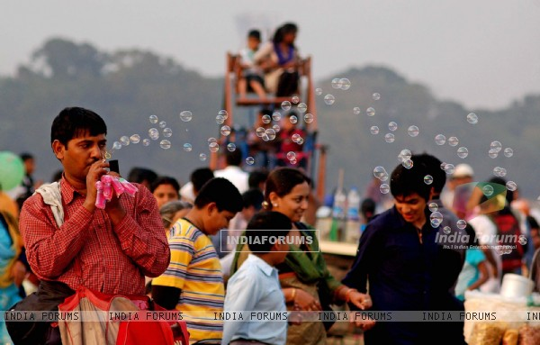 A hawker trades while tourists enjoy first day of New Year 2011 in Kolkata Maidan on Saturday. .