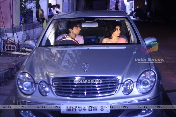 Sonu Sood and Soha Ali sitting on a car