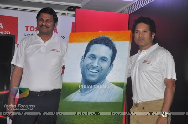 Sachin Tendulkar poses with his portrait at the launch 'WeAreSachin' campaign