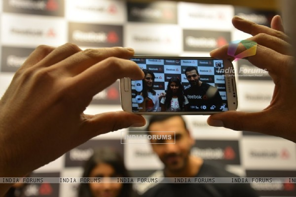 A fan clicking pic with John Abraham and Nargis Fakhri at the Press Meet of Reebok