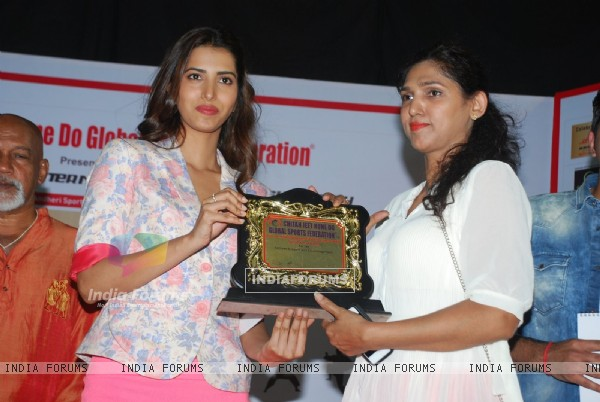 Manasvi Mamgai giving an award to a winner at Chita Jeet Kune Do Global Sports Acadamy