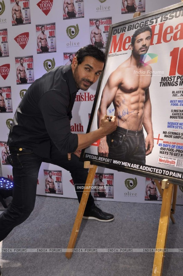 John Abraham signs his autograph at the Cover of Men's Health March Edition