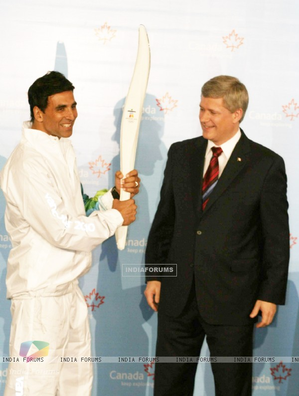 Canadian Prime Minister Stephen Harper and Bollywood Actor Akshay Kumar pose with a jacket, which will be worn by torchbearers for the 2010 Winter Olympics torch relay during an event at Trident in Mumbai on Monday, 16 November 2009